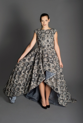 Sweeping grey floral gown, high neckline, cap sleeves, open scooped back filled with silk organza flowers, high-low floor-length skirt.